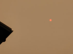reddish brown sky with red-orange sun